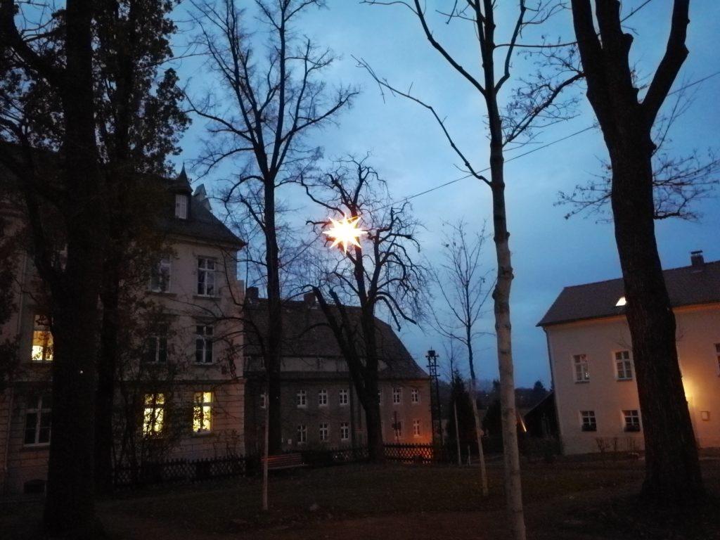 Herrnhuter Adventsstern leuchet im Gemeingarten des Kirchensaals in Kleinwelka