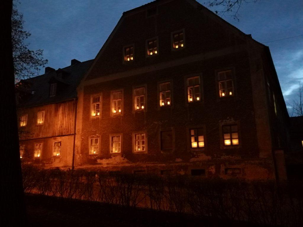Die Fenster des Schwesternhauses sind durch Kerzen hell erleuchtet.